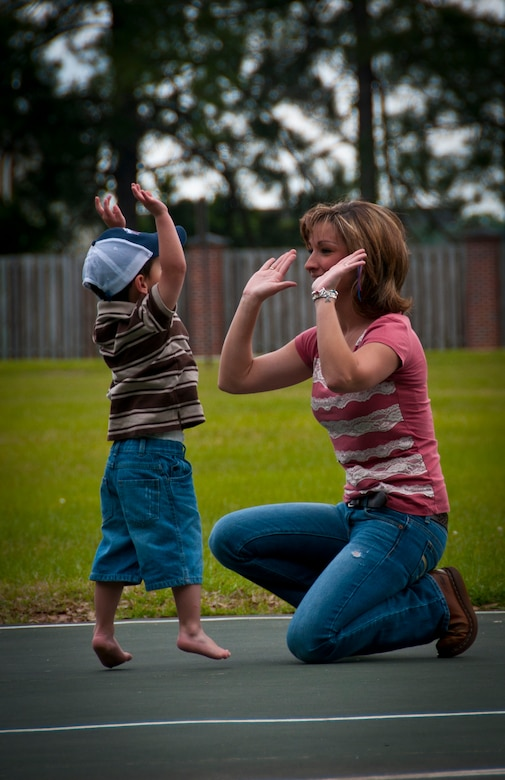 Three-year-old Hunter, and his mother Tricia, wife of Staff Sgt. Justin Hoffman, 15th Airlift Squadron loadmaster, 437th Airlift Wing, give each other a high-five after playing basketball at a Joint Base Charleston – Air Base park April 14. Hunter was recently diagnosed with moderate to severe classical autism. Hunter struggles with speaking, making eye contact and basic social skills. Even though Hunter struggles with simple things such as speaking or social interactions, he is very coordinated and can retain large amounts of information. (U.S. Air Force photo by Airman 1st Class Dennis Sloan)