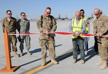 KANDAHAR AIR FIELD, Afghanistan — Air Force Col. Benjamin Wham, U.S. Army Corps of Engineers Afghanistan Engineer District South commander (left), Labib Bardawil, Contrack Inc. area manager (center), and Air Force Col. Sam Grable, 451st Air Expeditionary Mission Support Group commander, cut the ceremonial ribbon that marks the completion of the fourth phase of a Kandahar Airfield expansion in southern Afghanistan, April 10, 2012.