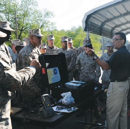Rafael Batista, future operations chief, Distribution Management Center, teaches a group of Marines April 5 how to use a portable deployment kit, which is used to track Marine Corps' equipment.