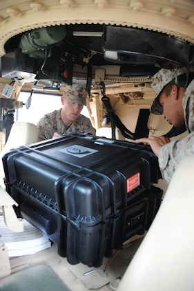 Lance Cpl. Edgar Galvan, right, heavy equipment operator, Combat Logistics Regiment 1, Camp Pendleton, Calif., and Lance Cpl. Nicholas Nation, landing support specialist, CLR 37, Okinawa, Japan, load a portable deployment kit inside a Humvee for training, April 5.::r::::n::::r::::n::