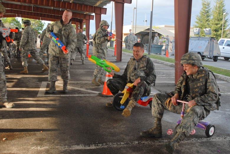 Capt. Michael Yamamoto (middle) and Maj. Malissa Golubic (right), both of the 144th Logistics Readiness Squadron, 144th Fighter Wing, Calif. National Guard, ride tricycles towards the end of the obstacle course during the 144th FW's Inaugural Combat Dining In held at the Fresno Air National Guard Base on April 14, 2012.   The combat dining in is steeped in tradition and helps build a unit's esprit de corps.  (Air National Guard photo by Senior Master Sgt. Chris Drudge)