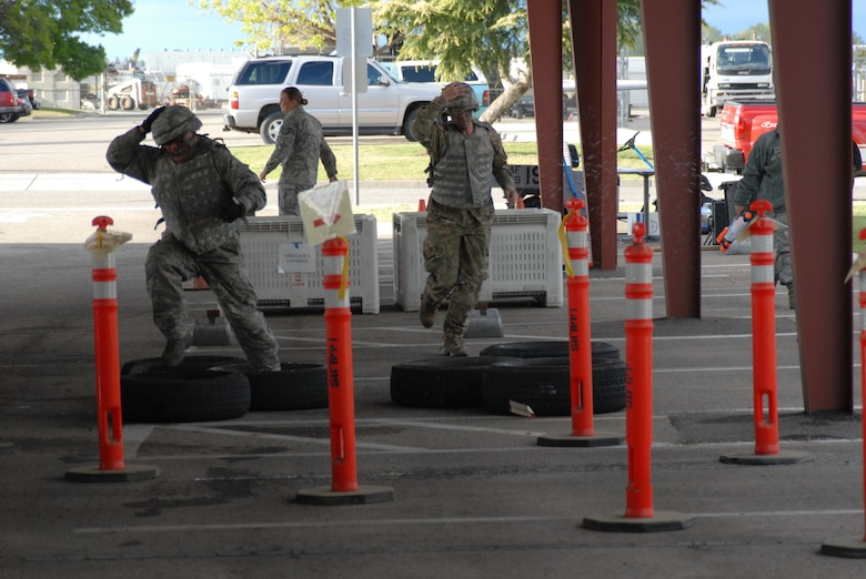 """Senior Master Sgt. Manuel Hernandez (left) and 2nd Lt. Nolan Bauer (right), both of the 144th Fighter Wing, Calif. National Guard, run the obstacle course on their way to the """"Grog"""" during the 144th FW's Inaugural Combat Dining In held at the Fresno Air National Guard Base on April 14, 2012.   The combat dining in is steeped in tradition and helps build a unit's esprit de corps.  (Air National Guard photo by Senior Master Sgt. Chris Drudge)"""