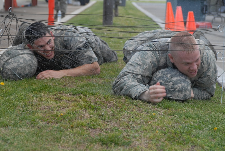 """Senior Airman Ryan Calzada (left) and 2nd Lt. Severin Koerner, both of the 144th Logistics Readiness Squadron, 144th Fighter Wing, Calif. National Guard, low crawl through the obstacle course on their way to the """"Grog"""" during the 144th FW's Inaugural Combat Dining In held at the Fresno Air National Guard Base on April 14, 2012.   The combat dining in is steeped in tradition and helps build a unit's esprit de corps.  (Air National Guard photo by Senior Master Sgt. Chris Drudge)"""