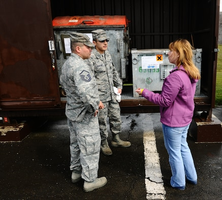 SPANGDAHLEM AIR BASE, Germany – Left to right, Master Sgt. Thomas McGrew and Staff Sgt. Jesus Martinez, 52nd Civil Engineer Squadron power production technicians, and Steffanie Metzger, U.S. Air Forces in Europe hazardous materials and waste manager, talk about proper labeling and upkeep of secondary storage containers during an Environmental, Safety and Occupational Health Compliance Assessment Management Program evaluation outside the power productions building here April 18. The week-long ESOHCAMP assessment gives the base an idea of how its compares to U. S. Air Force and host-nation regulations regarding environmental and occupational safety. This team is made up of 15 USAFE evaluators who assess Spangdahlem AB's overall health. The base uses the results from the program to help become USAFE's most environmentally friendly wing. (U.S. Air Force photo by Airman 1st Class Dillon Davis/Released)