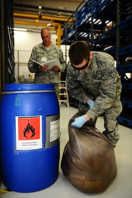 SPANGDAHLEM AIR BASE, Germany – Staff Sgt. Dustin Majewski, 52nd Component Maintenance Squadron propulsion support technician, empties a hazardous waste container while Master Sgt. Chad Haughenbury, U.S. Air Forces in Europe hazardous materials manager, inspects the work center during an Environmental, Safety and Occupational Health Compliance Assessment Management Program evaluation inside the jet propulsion maintenance shop here April 18. The week-long ESOHCAMP assessment gives the base an idea of how its compares to U. S. Air Force and host-nation regulations regarding environmental and occupational safety. This team is made up of 15 USAFE evaluators who assess Spangdahlem AB's overall health. The base uses the results from the program to help become USAFE's most environmentally friendly wing. (U.S. Air Force photo by Airman 1st Class Dillon Davis/Released)