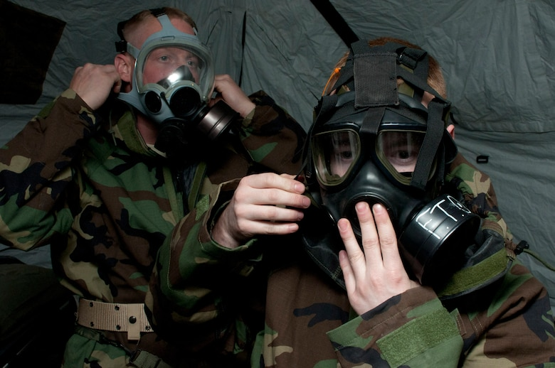 Senior Airman Craig M. Vonholtum from the 208th Weather Flight of the Minnesota Air National Guard and Lance Corporal Brandon Bergman from Marine Wing Support Squadron 471 US Naval- Marine Corps Reserve Readiness Center secure their gas masks during a simulated chemical attack Apr. 14, 2012. Sixteen members of the 208th along with three U.S. Marines from the Marine Wing Support Squadron 471 US Naval- Marine Corps Reserve Readiness Center Minneapolis are taking part in a field training exercise during week of Apr. 8, 2012. USAF photo by Tech. Sgt. Erik Gudmundson