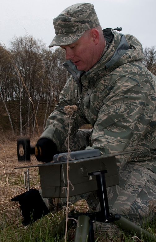 Senior Airman Robert T. Zweber, 208th Weather Flight of the Minnesota Air National Guard, pounds stakes into the ground to hold down a lightning detector at William O'Brien State Park Apr. 13, 2012. Sixteen members of the 208th along with three U.S. Marines from the Marine Wing Support Squadron 471 US Naval- Marine Corps Reserve Readiness Center Minneapolis are taking part in a field training exercise. USAF photo by Tech. Sgt. Erik Gudmundson
