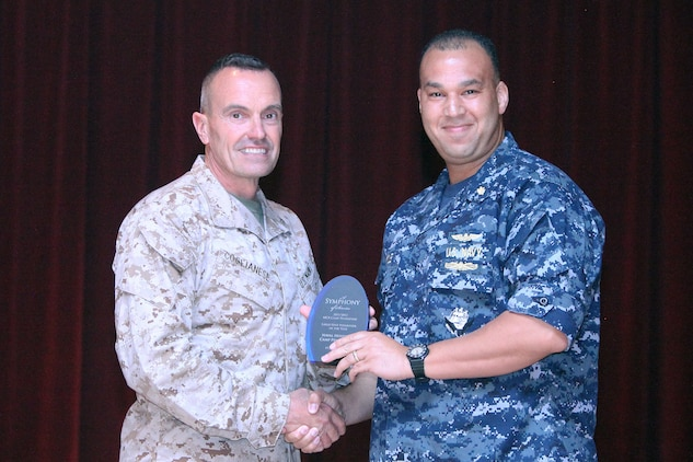 Navy Capt. Theron C. Toole (right), chief of medical staff, accepts an award from Brig. Gen. Vincent Coglianese (left), commanding general of Marine Corps Installations West, for Large Unit Volunteer of the Year on behalf of Naval Hospital, Camp Pendleton during a volunteer recognition ceremony at the Pacific Views Event Center at Camp Pendleton, Calif., April 19. The unit served more than 18,000 hours in 2011 coordinating food and toy drives, festivals, coaching Special Olympics athletes, the School to Center Program, assisting the Wounded Warriors Program, and providing services both on and off base.