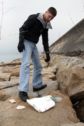 Volunteer Bryan J. Cowin stares down at the trash that has been washed ashore on the seawall north of Penny Lake aboard Marine Corps Air Station Iwakuni April 20, 2012. April 22 was established as International Earth Day in 1970 by the United Nations.