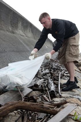 Volunteer Chad A. Welsh fills his trash bag with pieces of an old foam buoy after searching through piles of driftwood at the seawall north of Penny Lake aboard Marine Corps Air Station::r::::n::Iwakuni April 20, 2012. The cleanup is an annual event that takes place every Earth Day.