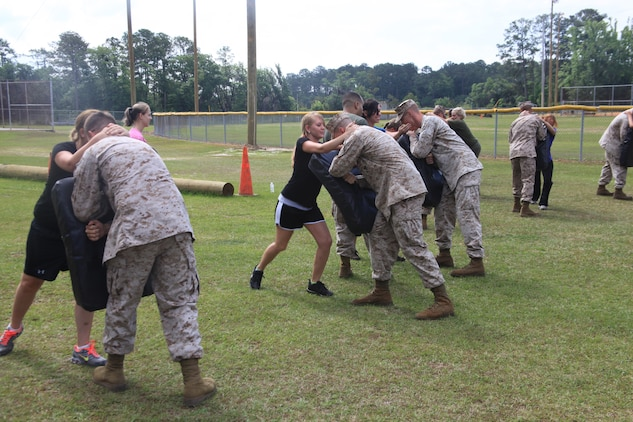 "Family members practice on their Marines during a period of Marine Corps Martial Arts Program instruction during the ""In Their Boots"" event, April 21. During the course of instruction, spouses executed several different techniques used by Marines."