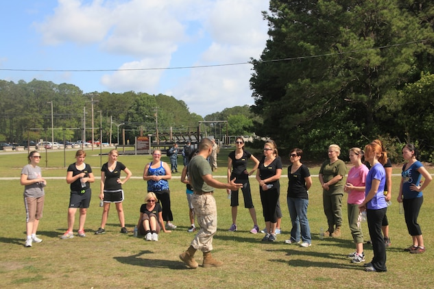 "Marine family members receive Marine Corps Martial Arts Program m instruction during the ""In Their Boots"" event April 21 near the Air Station obstacle course. Marine Corps Mar¬tial Arts Program was one of many events that took place throughout the day.::r::::n::::r::::n::"