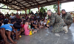 """U.S. Navy Lt. Gary W. Foshee (second from right), command chaplain, Combat Logistics Battalion 3, Marine Corps Base Hawaii, tells a bible story to Santa Juliana villagers during a worship service held in the local multipurpose room, April 22. Together members of the village, Armed Forces of the Philippines and U.S. service members repaired two water pumps, hung tire swings in common areas, renovated the local schoolhouse and donated books and school supplies to children in need during Exercise Balikatan 2012. Balikatan, which means """"shoulder to shoulder"""" in Filipino, is an annual training event aimed at improving combined planning, combat readiness, humanitarian assistance and interoperability between the Armed Forces of the Philippines and United States."""