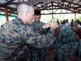 """U.S. Navy Lt. Gary W. Foshee, command chaplain, Combat Logistics Battalion 3, Marine Corps Base Hawaii, baptizes members of the Philippine Marine Corps during a worship service held in the local multipurpose room April 22. Together villagers, Armed Forces of the Philippines and U.S. service members repaired two water pumps, hung tire swings in common areas, renovated the local schoolhouse and donated books and school supplies to children in need during Exercise Balikatan 2012. Balikatan, which means """"shoulder to shoulder"""" in Filipino, is an annual training event aimed at improving combined planning, combat readiness, humanitarian assistance and interoperability between the Armed Forces of the Philippines and United States."""