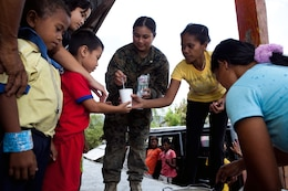 """U.S. Navy Petty Officer 1st Class Heidebelle Queddeng, field medical corpsman, Combat Logistics Battalion 3, Marine Corps Base Hawaii, helps serve a community meal to Santa Juliana villagers in the local multi-purpose room April 22. Together villagers, Armed Forces of the Philippines and U.S. service members repaired two water pumps, hung tire swings in common areas, renovated the local schoolhouse and donated books and school supplies to children in need during Exercise Balikatan 2012. Balikatan, which means """"shoulder to shoulder"""" in Filipino, is an annual training event aimed at improving combined planning, combat readiness, humanitarian assistance and interoperability between the Armed Forces of the Philippines and United States."""