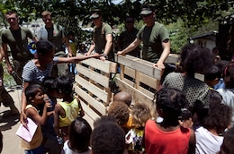 """U.S. Marines participating in Exercise Balikatan 2012 repair a school in the Santa Juliana Village as children watch, April 23. Together villagers, Armed Forces of the Philippines and U.S. service members repaired two water pumps, hung tire swings in common areas, renovated the local schoolhouse and donated books and school supplies to children in need during Balikatan, which means """"shoulder to shoulder"""" in Filipino. BK12 is an annual training event aimed at improving combined planning, combat readiness, humanitarian assistance and interoperability between the Armed Forces of the Philippines and United States."""