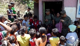 """U.S. service members participating in Exercise Balikatan 2012 pass out new shoes to students at a local schoolhouse in the village of Santa Juliana, April 23. Together villagers, Armed Forces of the Philippines and U.S. service members repaired two water pumps, hung tire swings in common areas, renovated the local schoolhouse and donated books and school supplies to children in need during Exercise Balikatan 2012. Balikatan, which means """"shoulder to shoulder"""" in Filipino, is an annual training event aimed at improving combined planning, combat readiness, humanitarian assistance and interoperability between the Armed Forces of the Philippines and United States."""