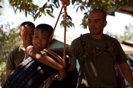 """Jacob Laurel, 9, swings on a tire recently hung by Armed Forces of the Philippines and U. S. service members in his village of Santa Juliana, April 23. Together with villagers and Armed Forces of the Philippines service members, Marines repaired two water pumps, hung tire swings in common areas, renovated the schoolhouse and donated books and school supplies to children in need during Exercise Balikatan 2012. Balikatan, which means """"shoulder to shoulder"""" in Filipino, is an annual training event aimed at improving combined planning, combat readiness, humanitarian assistance and interoperability between the Armed Forces of the Philippines and United States"""