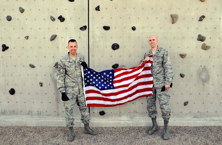 Master Sgt. Curtis Wilson, left, and his brother, Capt. Heath Wilson, display the flag used during an April 2012 reenlistment ceremony that had Sergeant Wilson and his brother rapelling from a wall at the U.S. Air Force Pararescue School at Kirtland Air Force Base, N.M. Sergeant Wilson has carried the flag during several deployments over his career and plans to present it to his brother when he retires. Sergeant Wilson is assigned to Air Force Operational Test and Evaluation Center Headquarters at Kirtland and Captain Wilson is assigned to the 99th Medical Group at Nellis AFB, Nev. (Photo by George Diamond).