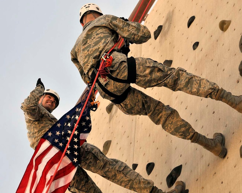 Master Sgt. Curtis Wilson, left, takes the oath of reenlistment being adminstered by his brother Capt. Heath Wilson as they rapell from a wall at the U.S. Air Force Pararescue School at Kirtland Air Force Base, N.M., in April 2012. Sergeant Wilson is a program manager at Air Force Operational Test and Evaluation Headquarters at Kirtland and Captain Wilson is a nurse with the 99th Medical Group at Nellis AFB, Nev. (Photo by George Diamond).