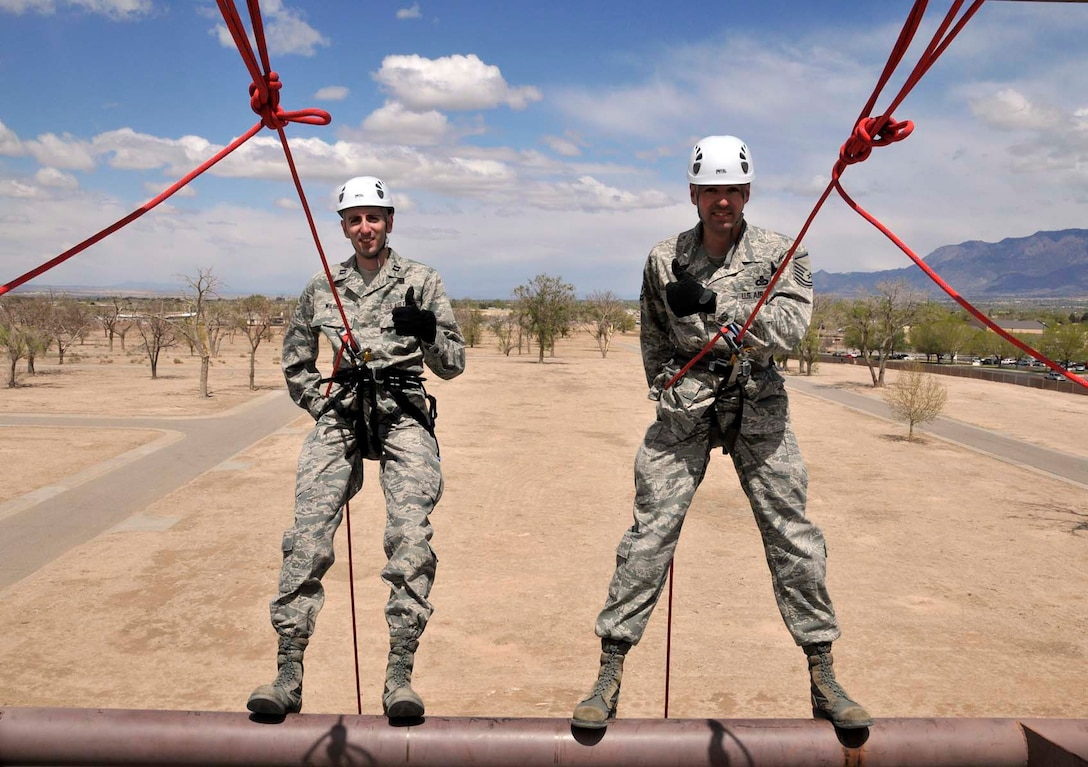 Capt. Heath Wilson, left, and his brother, Master Sgt. Curtis Wilson, prepare to rappel from a wall at the U.S. Air Force Pararescue School at Kirtland Air Force Base, N.M., in April 2012 so that Captain Wilson can administer the oath of reenlistment to Sergeant Wilson. Captain Wilson is assigned to the 99th Medical Group at Nellis AFB, Nev., and Sergeant Wilson is assigned to Air Force Operational Test and Evaluation Center Headquarters at Kirtland. (Photo by George Diamond).