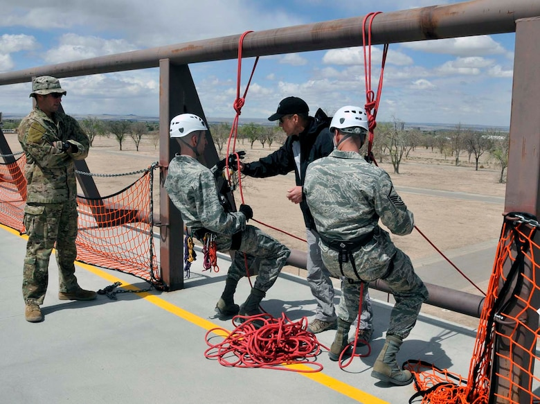 Master Sgt. Curtis Wilson, right, watches as his brother, Capt. Heath Wilson, listens to instructions from U.S. Air Force Pararescue School instructors at Kirtland Air Force Base, N.M., about how to rappel from a wall in preparation for Sergeant Wilson's reenlistment ceremony in April 2012. Sergeant Wilson is assigned to Air Force Operational Test and Evaluation Center Headquarters at Kirtland and Captain Wilson is stationed at Nellis AFB, Nev. (Photo by George Diamond).