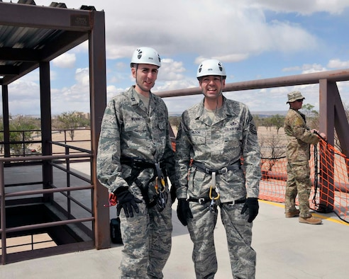 Master Sgt. Curtis Wilson, right, and his brother, Capt. Heath Wilson, prepare for a rappelling lesson in April 2012 from U.S. Air Force Pararescue School instructors at Kirtland Air Force Base, N.M., before Sergeant Wilson's brother administered the reenlistment oath while both rappelled from a wall. Sergeant Wilson is a program manager for Command and Control Systems at Air Force Operational Test and Evaluation Center Headquarters at Kirtland and Captain Wilson is the Element Leader of the Multi-Service Unit with the 99th Medical Group In-patient Squadron at Nellis AFB, Nev. (Photo by George Diamond).