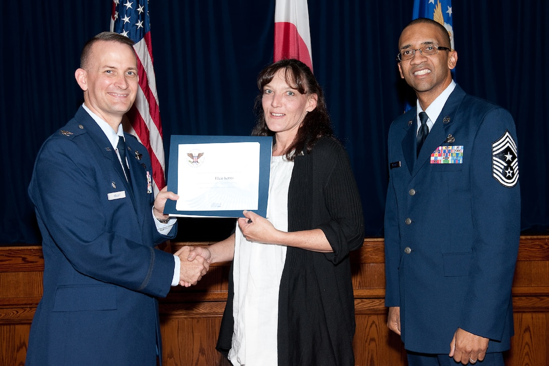 YOKOTA AIR BASE, Japan -- Ellen Kerns (center) receives the Presidential Volunteer Service Gold Awards from Col. Bill Knight (left), 374th Airlift Wing commander, and Command Chief Master Sgt. Ronald Draper (right), 374th Airlift Wing, during Yokota's Annual Volunteer Recognition Ceremony at Yokota Air Base, Japan, April 19, 2012. The Presidential Volunteer Service Award recognizes individuals and groups for their dedicated service over the past year and for their cumulative lifetime volunteer service. The gold award winners have provided and documented over 500 hours of volunteer service in 2011. (U.S. Air Force photo/Osakabe Yasuo)