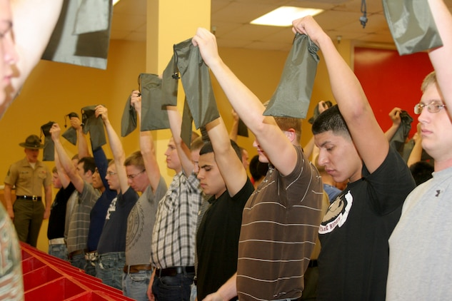 Recruits hold up green-money valuable bag that is issued to them in the contraband room during receiving April 23 aboard Marine Corps Recruit Depot San Diego. Recruits are issued a 'war bag' which consist of basic gear that the recruits will utilize throughout recruit training.