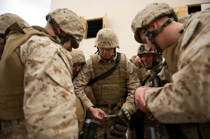 JOINT BASE ELMENDORF-RICHARDSON, Alaska -- Marine Cpl. Terrence Nuss (center), a D Company, Anti-Terrorism Battalion squad leader, shares smartphone footage of his Marines maneuvering during training in urban operations April 21 at JBER's Baumeister City MOUT Complex. (U.S. Air Force photo/David Bedard)