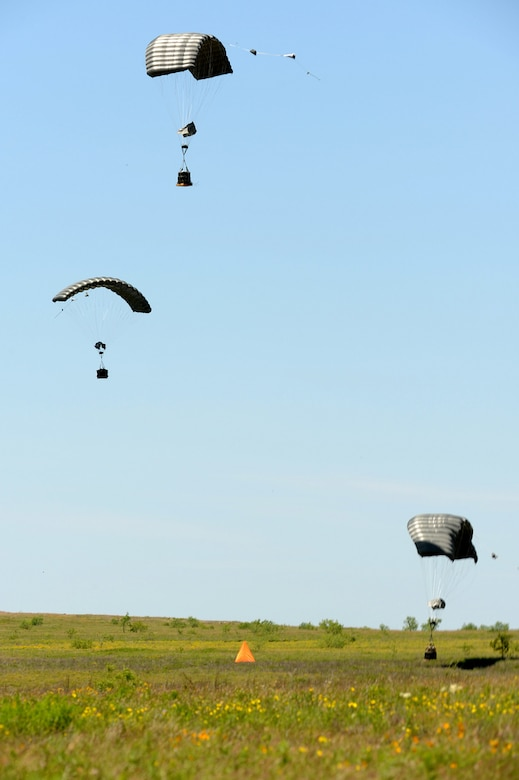 Joint Precision Airdrop System (JPADS) bundles land close to the intended target during a training exercise Tuesday, April 24, at the Antelope Drop Zone at Fort Hood. JPADS is an airdrop system that uses Global Positioning Satellite, steerable parachutes and an onboard computer to steer loads to a designated point of impact on a drop zone. (Photo by Daniel Cernero, III Corps and Fort Hood Public Affairs)