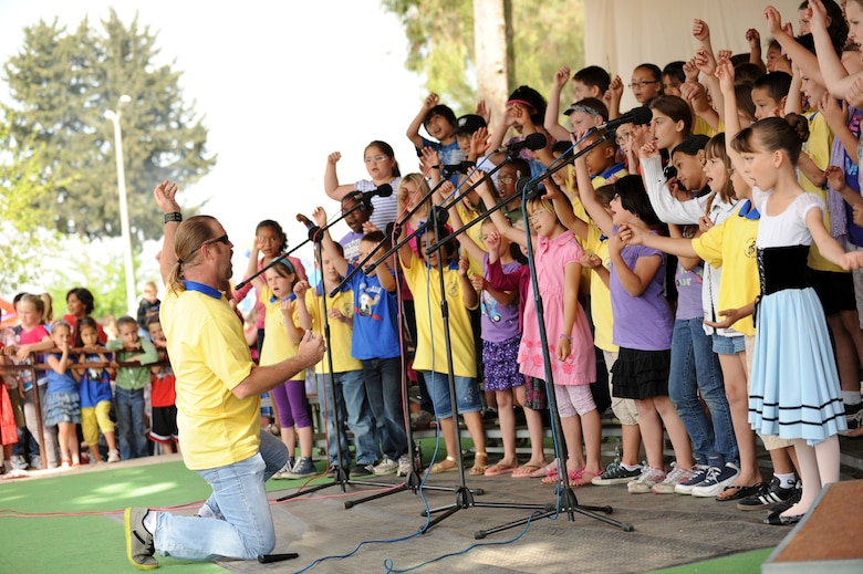 Shannon Daniels, Incirlik Unit School kindergarten through fifth grade music teacher, leads his students during a performance at a Children's Day festival April 22, 2012, at Incirlik Air Base, Turkey. The event was hosted by the Turkish air force 10th Tanker Base Command and was open to all Turkish and American members of Team Incirlik. The event offered an opportunity for camaraderie and building partnership between Turkish and American service members and civilians. Children's Day is a national holiday that honors Turkish children and the future of the country. (U.S. Air Force photo by Senior Airman Jarvie Z. Wallace/Released)