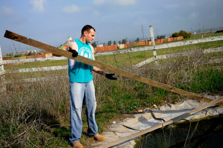 Staff Sgt. Kevin Kirk, 39th Logistics Readiness Squadron, removes fence boards from a pond at the base dog park April 21, 2012, at Incirlik Air Base, Turkey. Twelve volunteers spent five hours gathering trash and debris, mending fences, and mowing to provide a place for the base's furry residents to play. (U.S. Air Force photo by Staff Sgt. Kali L. Gradishar/Released)