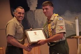 Brig. Gen. Vincent A. Coglianese, commanding general of Marine Corps Installation West - Marine Corps Base Camp Pendleton presents the 'Honor Medal with crossed palms' certificate to Connor F. Stotts, an Eagle Scout with Camp Pendleton's Boy Scout Troop 790. Stotts was presented the coveted Boy Scouts of America 'Honor Medal with crossed palms'. Stotts was awarded the medal in recognition for single handedly saving the lives of three swimmers, July 31, 2011.