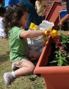 Makayla Parker plants a flower during the Joint Base Charleston - Air Base's event Child Development Center's Gardening with Parents April 20. Makayla's father is Tech. Sgt. Marcus Parker, 437th Maintenance Operations Squadron. (U.S. Air Force photo/Airman 1st Class Chacarra Walker)
