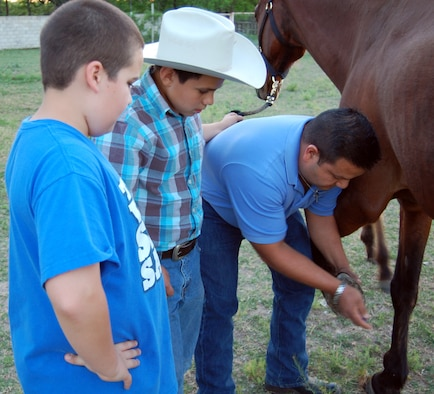 Memo Montejano, an Amistad Physical Therapy technician, demonstrates how to clean out the hooves of a horse to his son Memo Jr. and Joshua Waid, at the Waid family home in Del Rio, Texas, April 17, 2012. Montejano and his son are 12-time successful horse rescuers and the Waid family is helping them care for a rescue horse at their residence. (U.S. Air Force photo/Jack Waid)