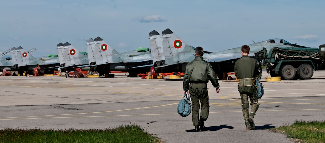Capt. Kirby Sanford, 555th Fighter Squadron F-16 Fighting Falcon pilot, and Bulgarian air force Maj. Ilia Doychinov, 1st Fighter Squadron commander, walk toward a line of MiG-29 and MiG-21 aircraft April 19, 2012, at Graf Ignatievo Air Force Base, Bulgaria. Sanford is deployed here from Aviano Air Base, Italy, with more than 500 personnel in support of exercise Thracian Star 2012.  The month-long training will provide the two air forces the opportunity to gain better insight into both the tactics of the pilots and the capabilities of the different aircraft. (U.S. Air Force photo/Senior Airman Katherine Windish)