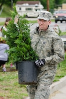 Capt. Allen Bear, 139th Environmental Management Officer, carries a small tree during an Earth Day event April 27, 2012 in St. Joseph, Mo. The 139th Airlift Wing donated 14 trees which were planted by the St. Joseph Parks and Recreation Department and students from Mark Twain Elementary School. (U.S. Air Force photo by Staff Sgt. Michael Crane/Missouri Air National Guard)