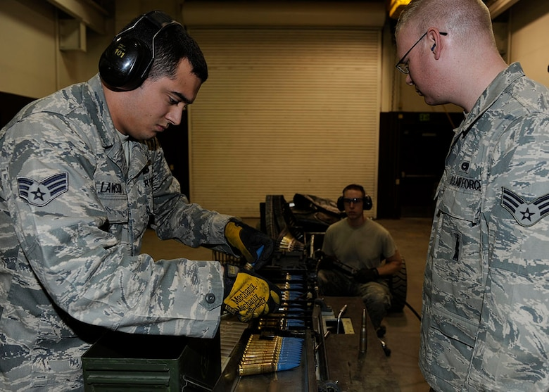 Members of the 3rd Munitions Squadron Conventional Maintenance use an ammunition loading system replenisher assembly to load 20-milimeter rounds into a universal ammunition loading system on Joint Base Elmendorf-Richardson, Alaska, April 26. The rounds will be used by F-22s to fire at a target banner during aerial combat training. (U.S. Air Force photo/Staff Sgt. Robert Barnett)