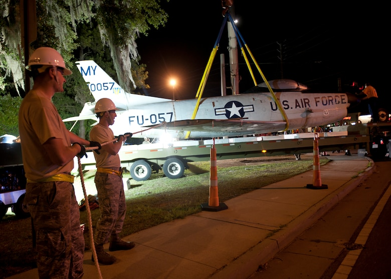 U.S. Air Force Staff Sgts. Ryan Adams-Brady and Christopher Matthews, 23d Equipment Maintenance Squadron, assist in guiding an F-86L Sabre onto a flatbed trailer that will transport it to Moody Air Force Base, Ga., April 24, 2012. The aircraft will be refurbished and then moved to the George W. Bush Air Park at Moody Field to commemorate the late Maj. Lyn McIntosh and the Flying Tigers heritage. (U.S. Air Force photo by Senior Airman Eileen Meier/Released)