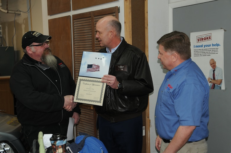 Steve and Mike Howard recieve a thank you certificates from Col. Peter Hronek for all the work they did in restoring a 2001 Honda CRV for the Recycled Rides.  (U.S. Air Force photos by Senior Master Sgt. Eric Peterson)