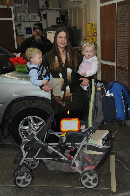 Senior Airman Sarah-Jane Lattin stands with her two children in front of the vehicle she received as part of the program. (U.S. Air Force photos by Senior Master Sgt. Eric Peterson)