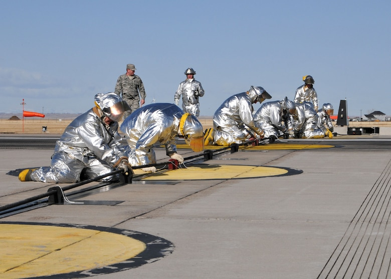 MTANG firefighters replace the barrier cable following a successful test of the end of runway aircraft arresting system.  The certification engagement exercise was held at the Great Falls International Airport on March 4.  (U.S. Air Force photo by Senior Master Sgt. Eric Peterson)