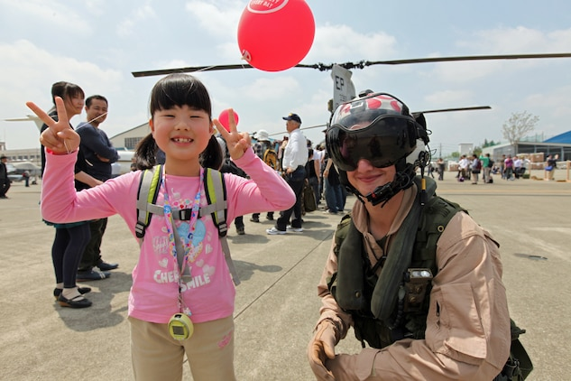 Lance Cpl. Ryan Petty, a crew chief with Marine Medium Helicopter Squadron 265 (REIN), 31st Marine Expeditionary Unit, poses with a Japanese girl during a static display of CH-46E Sea Knight helicopters at the Atsugi Air Show, Atsugi Naval Air Facility, Japan, on April 28. The Marines' participation in the event comes one year after their assistance to Japanese tsunami victims during Operation Tomodachi. The 31st MEU is the United States' expeditionary force in readiness for the Asia Pacific region.