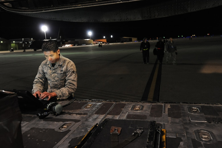 U.S. Air Force Airman 1st Class Alejandro Jasso, 27th Special Operations Aircraft Maintenance Squadron crew chief, looks up inspections cards for job performance on the flightline at Cannon Air Force Base, N.M., Feb. 21, 2012. The laptop is referred to as a ?Go Book? and contains information for every job or duty needed to be performed by the crew member. (U.S. Air Force photo by Senior Airman Jette Carr)