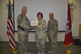 KANDAHAR AIRFIELD, Afghanistan — Col. Benjamin Wham, U.S. Army Corps of Engineers Afghanistan Engineer District-South commander (left), and Command Sgt. Maj. Lorne Quebodeaux (right), present Kelly Gilhooly with the Achievement Medal for Civilian Service Apr. 21. Gilhooly deployed to the South District from Rock Island, Ill. to serve as the process improvement manager.