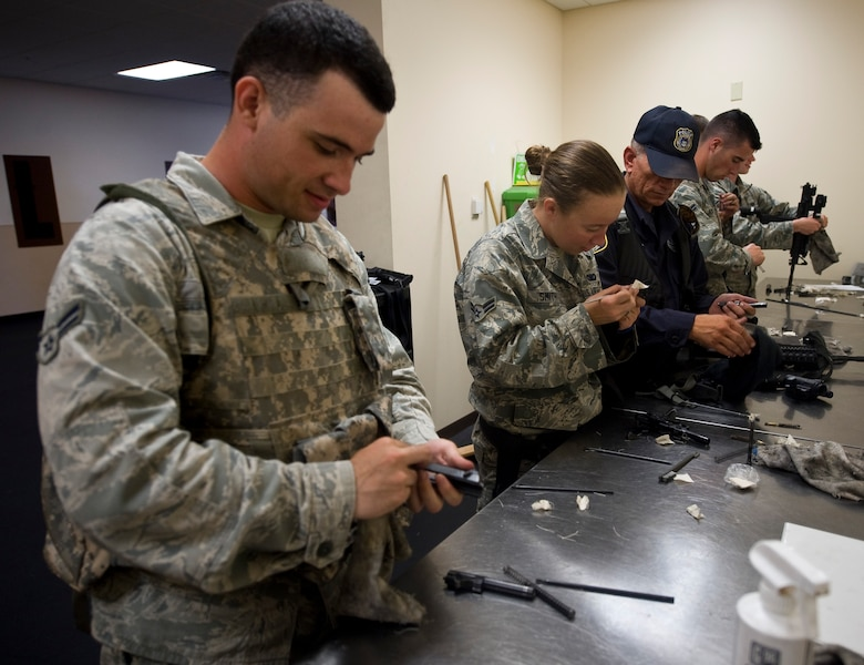 Personnel from the 2nd Security Forces Squadron clean their weapons in the 2 SFS guard mount room on Barksdale Air Force Base, La., July 31. If their weapons are due for cleaning, they must pass an inspection by the armorers before the Airman is allowed to return the weapon. (U.S. Air Force photo/Staff Sgt. Chad Warren)(RELEASED)