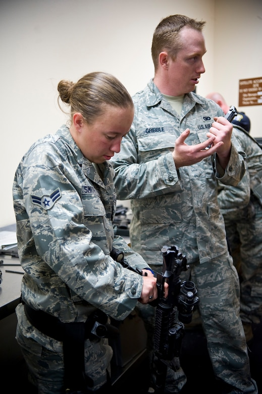 Airman 1st Class Ellen Smith and Senior Airman Nicholas Gribble, 2nd Security Forces Squadron, clean their weapons in the 2 SFS guard mount room on Barksdale Air Force Base, La., July 31. Personnel must clean their weapons every two weeks, even if they have not been fired, to ensure they are in optimal working condition. (U.S. Air Force photo/Staff Sgt. Chad Warren)(RELEASED)