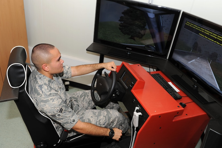 SPANGDAHLEM AIR BASE, Germany – Airman 1st Class George Puhlman, 52nd Mission Support Group knowledge operations manager, trains on the stick shift simulator here July 30. The simulator uses computer based training to teach people basic driving techniques to ensure they are trained on how to drive in Europe. (U.S. Air Force photo by Senior Airman Christopher Toon/Released)