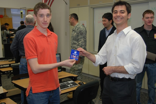 John Feller (r), Japan District Engineer, presents a gift card to David Bordenave who earned the first place during the 2012 West Point Bridge Design Contest. (Official Japan Engineer District photo by T.W. Lyman)